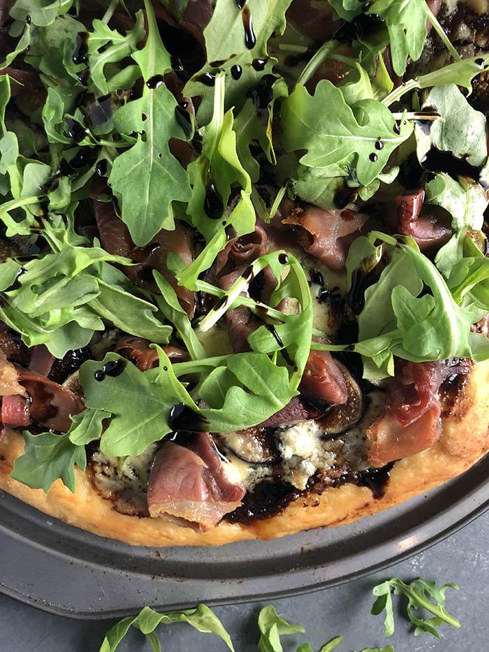 Arugula atop a fig prosciutto pizza