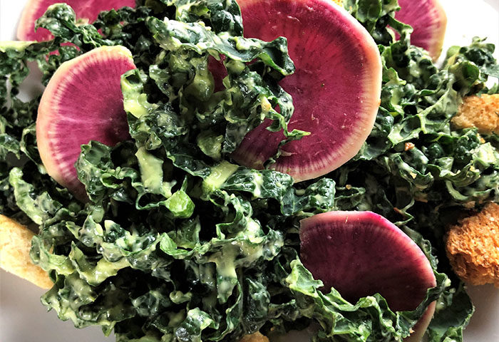 lacinato kale with creamy avocado dressing and watermelon radishes on a white plate
