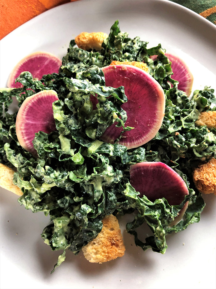 acinato kale with creamy avocado dressing and watermelon radishes on white plate
